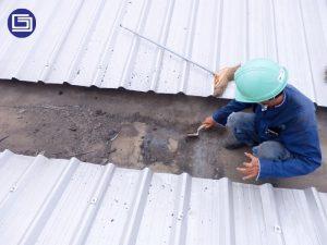 Pembersihan talang lama dari debu dan lumpur sebelum pelapisan komposit fiberglass.