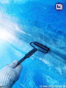Menggunakan roll besi untuk mencegah gelembung pada laminasi fiberglass.